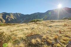Rayons de lumière du soleil lumineux brillant au-dessus des montagnes d'automne photographie stock libre de droits