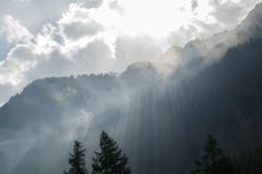 Rayons de soleil au-dessus d'arête boisée de montagne image libre de droits
