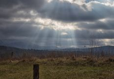 Rayons de soleil au-dessus d'une vallée fumeuse de montagne Photographie stock libre de droits