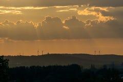 Rayons de soleil du coucher du soleil frappant quelques turbines de vent photos stock