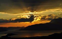 Rayons de soleil et le coucher du soleil avec un ciel orange Image stock