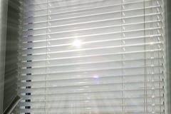 Rayons de soleil faisant leur voie par les abat-jour Images stock