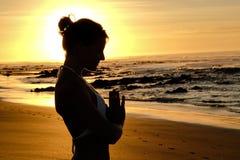 Rayons de soleil lumineux derrière la silhouette de formation principale de yogi Image stock