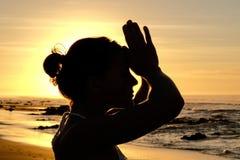 Rayons de soleil lumineux derrière la silhouette de formation principale de yogi Photo stock