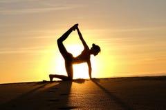 Rayons de soleil lumineux derrière la silhouette de formation principale de yogi Photo libre de droits