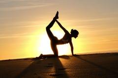Rayons de soleil lumineux derrière la silhouette de formation principale de yogi Images stock