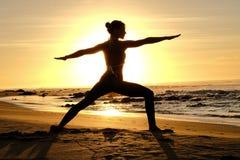 Rayons de soleil lumineux derrière la silhouette de formation principale de yogi Image libre de droits