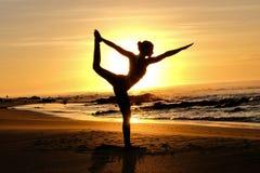 Rayons de soleil lumineux derrière la silhouette de formation principale de yogi Photographie stock