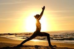 Rayons de soleil lumineux derrière la silhouette de formation principale de yogi Photos stock