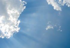 Rayons de soleil par les nuages blancs pelucheux dans un ciel bleu Image libre de droits