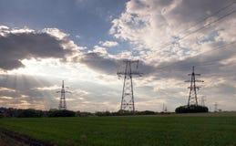Rayons de Sun au-dessus des lignes à haute tension de distribution électrique Rayons du s Photographie stock libre de droits