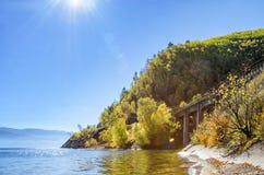 Rayons de Sun dans la nature avec la belle eau, le coût et le pont de pierre près de la montagne Image stock