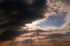 Rayons et nuages noirs de Sun Photographie stock libre de droits