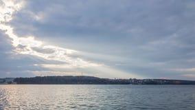 Rayons incroyables du soleil se déplaçant au-dessus du paysage de lac de ville Laps de temps clips vidéos