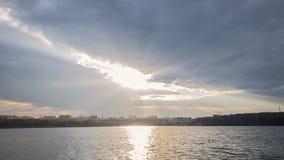 Rayons incroyables du soleil se déplaçant au-dessus du paysage de lac de ville Laps de temps banque de vidéos