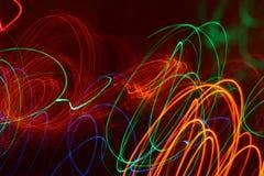 Rayons légers colorés dessinant les modèles de résumé dans l'obscurité Photographie stock libre de droits
