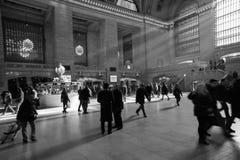 Rayos de la luz del sol dentro de la estación de Grand Central con la gente que camina en el tiempo de la precipitación Imagenes de archivo
