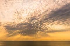 Rayos de la luz que brillan abajo de la nube del cielo con el mar Fotos de archivo