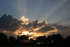 Rayos de la puesta del sol en una tarde nublada Foto de archivo