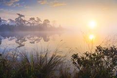 Rayos de la salida del sol sobre el lago con la niebla de la reflexión en el agua, Imagenes de archivo