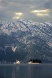 Rayos de sol que aligeran la iglesia en el fiordo tempestuoso de las montañas fotografía de archivo libre de regalías