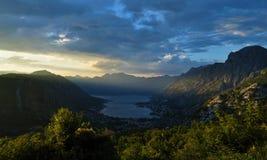 Rayos de sol que iluminan la montaña de Lovcen y la ciudad y la bahía de Kotor en la oscuridad imagen de archivo