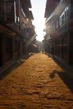 Rayos de Sun de la mañana del callejón del guijarro del ladrillo de Bhaktapur Imágenes de archivo libres de regalías