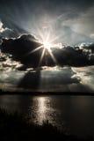 Rayos de Sun detrás de las nubes sobre el lago Fotos de archivo libres de regalías