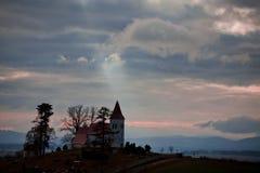 Rayos del sol que señalan a la iglesia en el horizonte fotografía de archivo libre de regalías
