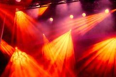 Rayos ligeros amarillos y rojos del proyector a través del humo en el teatro o la sala de conciertos Reflector del pasillo de la  fotografía de archivo libre de regalías