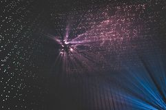 Rayos ligeros a través de los pequeños agujeros en un espacio oscuro fotografía de archivo