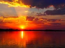 Rayos pasados del cielo anaranjado de la puesta del sol sobre el agua/el río foto de archivo