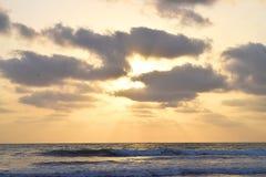 Rayos solares brillantes de oro que vienen a través de las nubes oscuras en cielo y sobre el océano Imagen de archivo libre de regalías