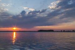 Rayos solares sobre un lago colorado en la salida del sol Fotografía de archivo