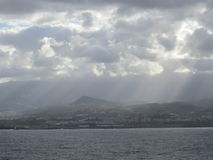 Rayos a través de las nubes para hacer que la isla brilla Imágenes de archivo libres de regalías