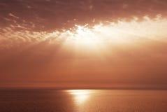 Rayos y nubes de la puesta del sol sobre el mar Foto de archivo libre de regalías