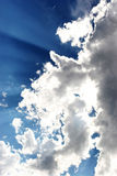 Rays in Cloud. Rays of Sun beaming through clouds in the blue sky Stock Image