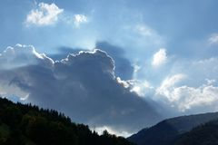 Rays and clouds. Rays through blue clouds over forests Stock Images