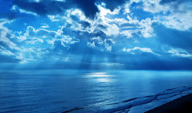 Rays Clouds Blue Sky Ocean. A blue sky with the suns rays shining on the ocean Stock Photo