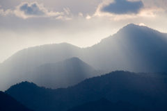 Rays of Light. Beams of light break through the clouds above the mountain peaks stock photos