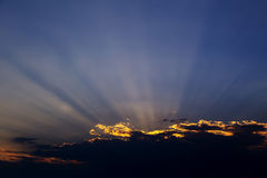 Rays of light, dramatic sunset. Rays of the sun escaping because of clouds Royalty Free Stock Images