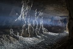 Abandoned limestone adit. The rays of light make their way through the entrance to the old dark cave royalty free stock photography