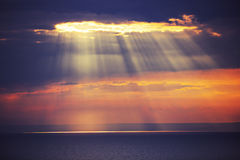 Rays of light shine in water. Dramatic sunset Royalty Free Stock Images
