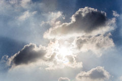 Rays of light shining through clouds with blue skys Royalty Free Stock Photo