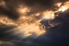 Rays of light shining through dark clouds Stock Photography