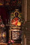 Rays of light shining onn an icon of Jesus Christ in an orthodox. Church in Bulgaria, with candles lit in front of it Royalty Free Stock Images