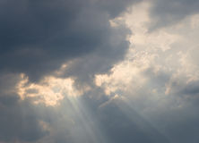 Rays of light shining throug  clouds Stock Photos