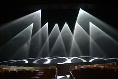 Rays of light on the stage during the show. On a dark background Stock Photography
