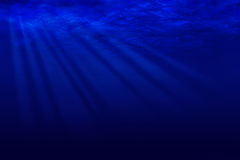 Rays of moonlight through the ocean water Royalty Free Stock Image