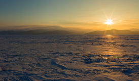 Rays of rising sun light up the snow covered ice. Royalty Free Stock Photo